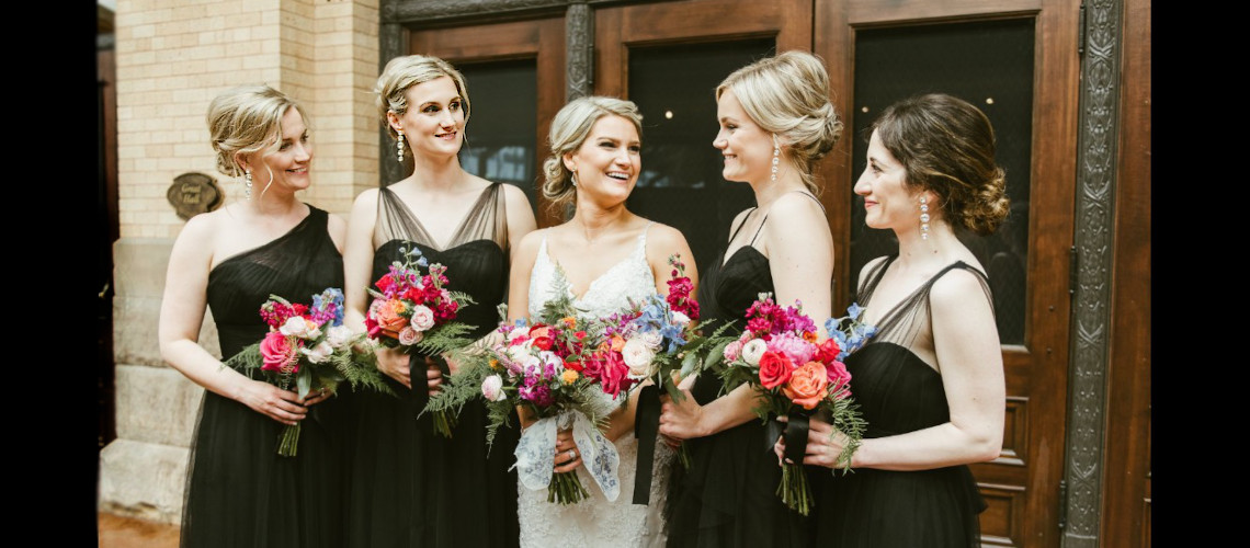 Bride and bridesmaids holding flowers outside wedding venue